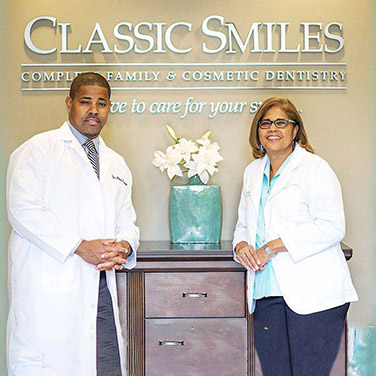 Drs. Susanne and Mikal Baaqee in front of Classic Smiles logo