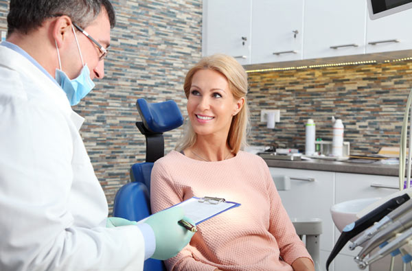 Woman talking to dentist during dental exam.